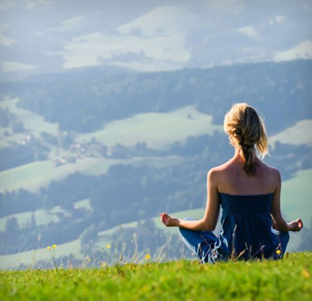 woman meditating on hill